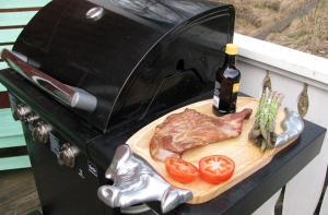 Rökt vildsvinsbog upplagd på skärbräda bredvid grillen tillsammans med tomat och färsk sparris.