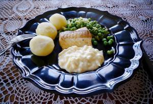 Rökt torsk upplagt på en svart tallrik med kokt potatis, ärtor och äggsås.