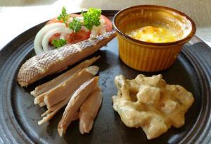Anka skuren och upplagd på tallrik med ostgratinerat potatismos, och några tomatskivor.