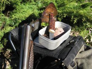 Skivat rökt hjärta i burk ute i skogen bredvid enbuske och brutet gevär.