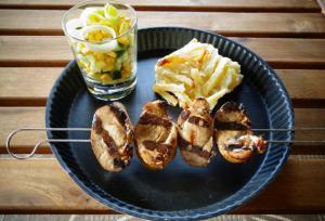 Grillad fläskfilé på spett med potatisgratäng samt sallad i glas på tallriken.